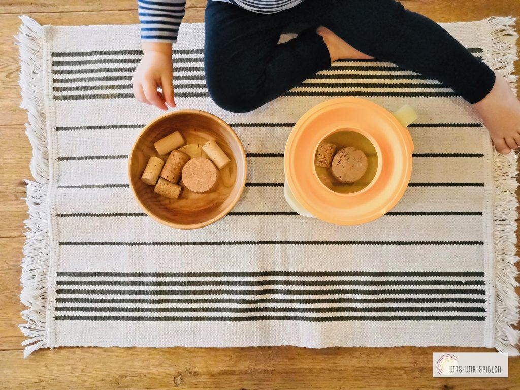 Füllübung mit Korken und einem Messbecher - ideal für Babys und Kleinkinder